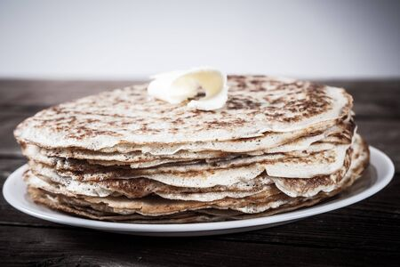blini: Stack of Russian pancakes - blini on a wite plate on old wooden table. Shallow depth of field.