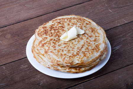 blini: Stack of Russian pancakes - blini on a wite plate on old wooden table. Stock Photo
