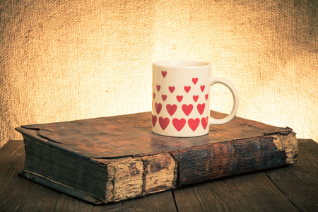 White mug with many pictured hearts and old book on the old wooden table on burlap background. Toned. photo