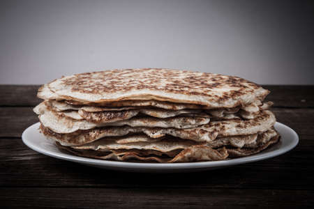 blini: Stack of Russian pancakes - blini on a wite plate on old wooden table. Toned. Stock Photo