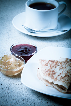 blini: Russian pancakes - blini with cup of tea and jam. Toned.