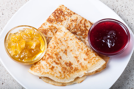 blini: Russian pancakes - blini with two kinds of jam. Stock Photo