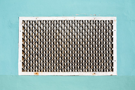 sidewall: Old metal patterned ventilation grid on the plastered wall.