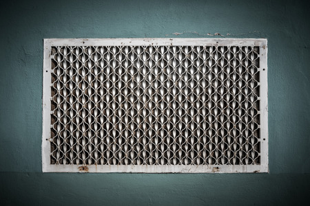 sidewall: Old metal patterned ventilation grid on the plastered wall. Toned. Stock Photo