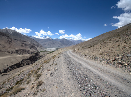 spring  tajikistan: The road in the mountains with snowy peaks and clouds in the blue sky.