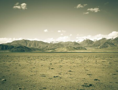 scorched: Rocky mountains and scorched valley on a background of blue sky with a few white clouds. Toned.