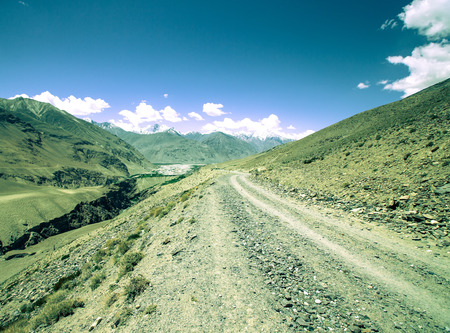 spring  tajikistan: The road in the mountains with snowy peaks and clouds in the blue sky. Toned.