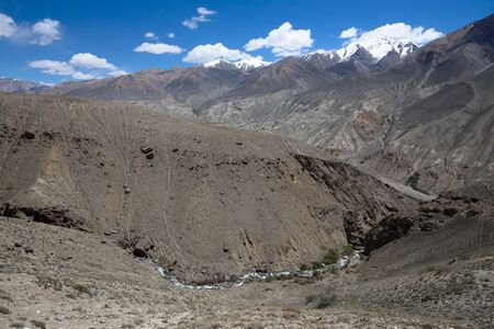 spring  tajikistan: Mountains with snow-capped peaks and clouds in the blue sky.