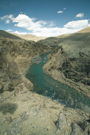 spring  tajikistan: The river in the mountains and clouds in the blue sky. Toned.