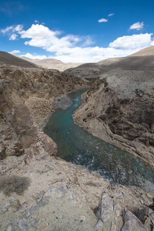 spring  tajikistan: The river in the mountains and clouds in the blue sky.
