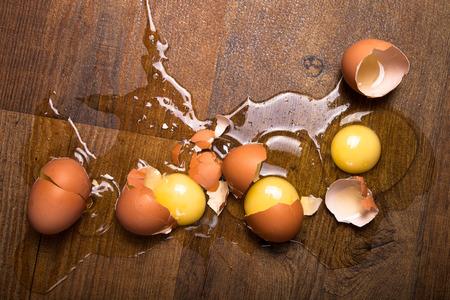 Gebroken eieren op de houten vloer.