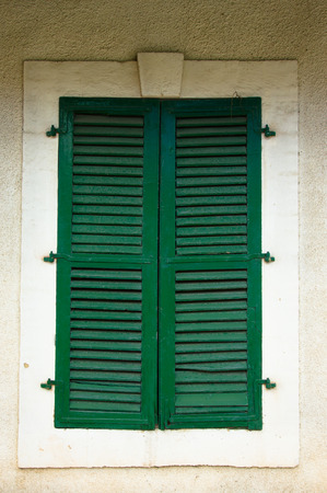 Old green window with closed shutters. photo