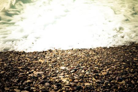 transformed: Wave se transforma en espuma en una playa de guijarros en Chipre. Poca profundidad de campo. Foto de archivo