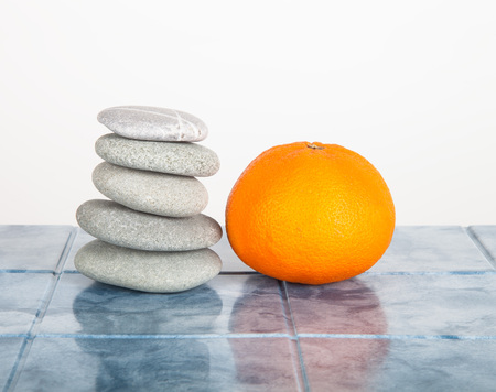 Stack of stones for spa procedures and orange on a table made of tiles photo