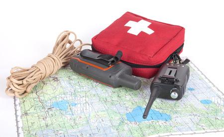 Kaart, gps navigator, draagbare radio, touw en EHBO-kit op een lichte achtergrond. Set badmeester. Stockfoto