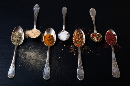 Old metal spoons with different kind of spices on a black background.