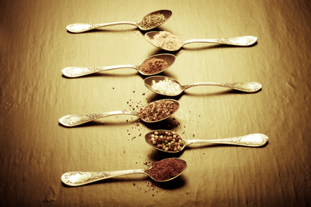 Old metal spoons with different kind of spices on a black background. Toned.