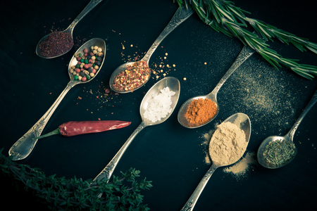 karri: Herbs and spices with old metal spoons on a black background. Toned.