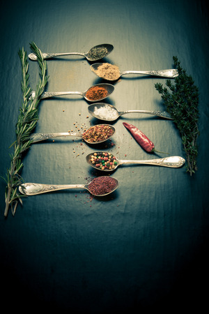 Herbs and spices with old metal spoons on a black background. Toned.