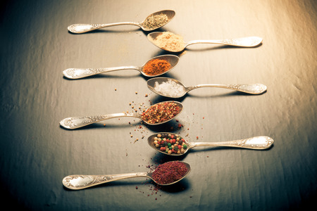 karri: Old metal spoons with different kind of spices on a black background. Toned.