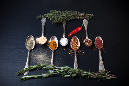 karri: Herbs and spices with old metal spoons on a black background.