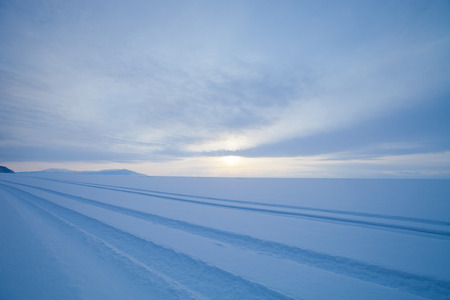 Traces of cars in the vast snowy wilderness. Lake Baikal in winter.