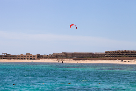 kiter: Kiter in the lagoon of the Red Sea on the background of an unfinished hotel. Egypt, Sharm El Sheikh.