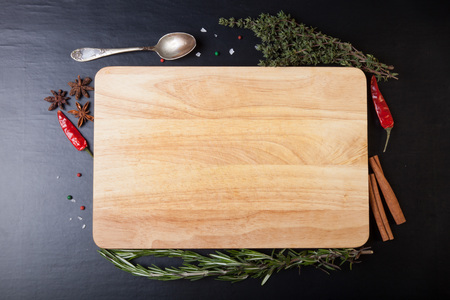 Cutting board with rosemary, thyme, colored and chili pepper, old spoon, cinnamon, cardamom and sea salt on a black background. Stock Photo