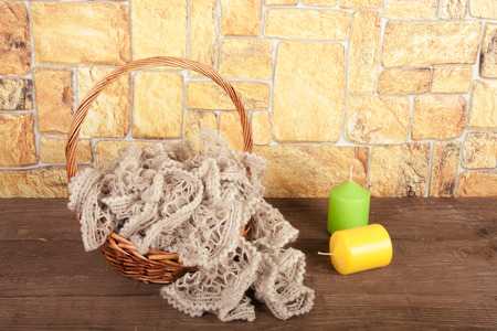 Knitted scarf in the basket and two color candles on wooden table opposite a stony wall. Toned. photo