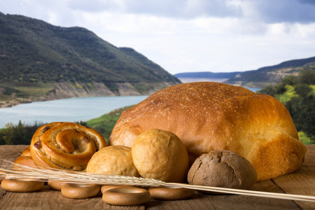 Bread assortment and wheat ears on an old wooden table opposite the mountains and river. photo