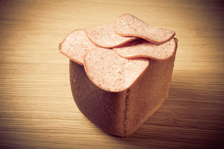 air dried salami: Half a loaf of rye bread with a few slices of sausage on a light wooden table. Toned. Stock Photo