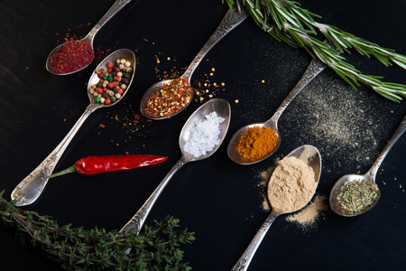 Herbs and spices with old metal spoons on a black background.