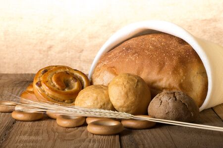 Bread assortment and wheat ears on an old wooden table. photo