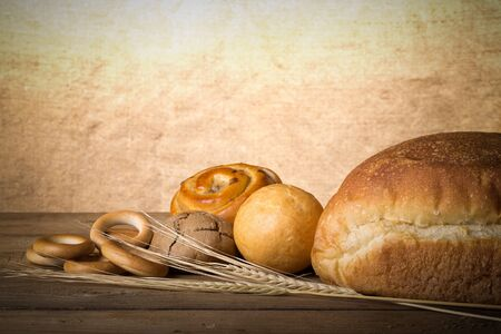 Bread assortment and wheat ears on an old wooden table. Toned. photo