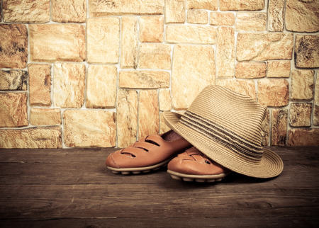 moccasins: Straw hat and moccasins on a wooden table in front of a stone wall. Toned.