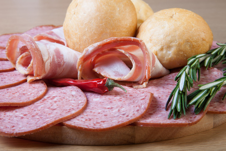 air dried salami: Slices of sausage and bacon on a cutting board with bread rolls, chilli pepper and rosemary. Toned.