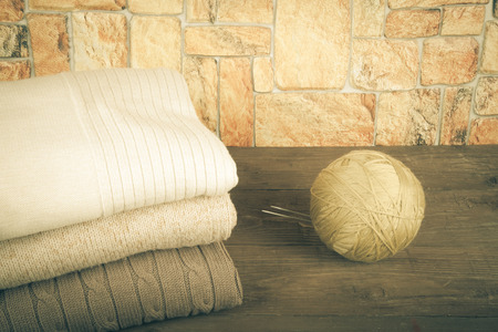 Stack of knitting clothes and ball of yarn with knitting needles on wooden table opposite a stony wall. Toned. photo