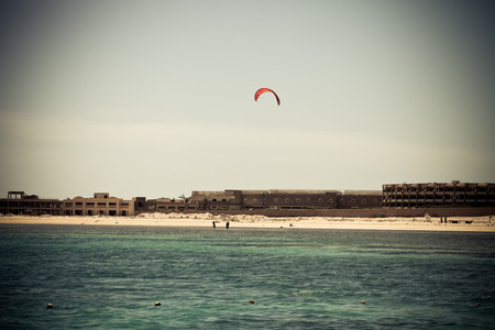 kiter: Kiter in the lagoon of the Red Sea on the background of an unfinished hotel. Egypt, Sharm El Sheikh. Toned.