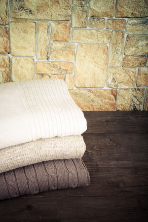 Stack of knitting clothes on wooden table opposite a stony wall. Toned. photo