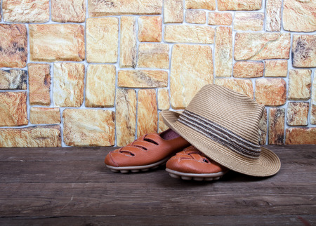 moccasins: Straw hat and moccasins on a wooden table in front of a stone wall.