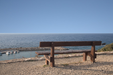 Wooden bench on the beach against the setting sun. photo