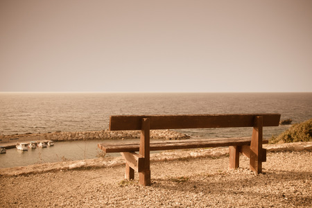 Wooden bench on the beach against the setting sun. Toned. photo