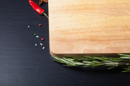 Cutting board with rosemary, colored and chili pepper, and sea salt on a black background. photo