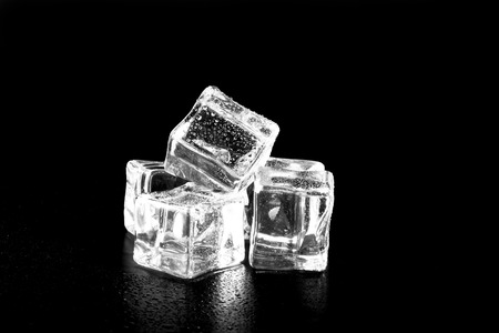 cubos de hielo: Ice cubes on black wet table. Selective focus. Foto de archivo