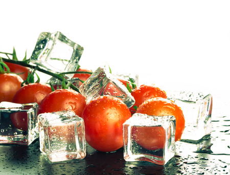 Banch of red cherry tomatos and ice cubes on white background. Selective focus.