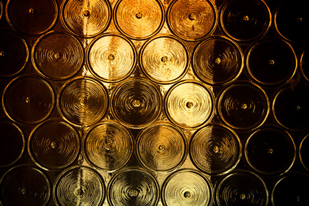Wall of glass bottles with somthing metall behind it. Selective focus. Toned. Stock Photo