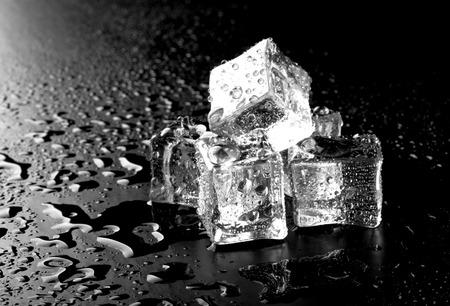 cubetti di ghiaccio: Cubetti di ghiaccio sul tavolo bagnato nero. Messa a fuoco selettiva.