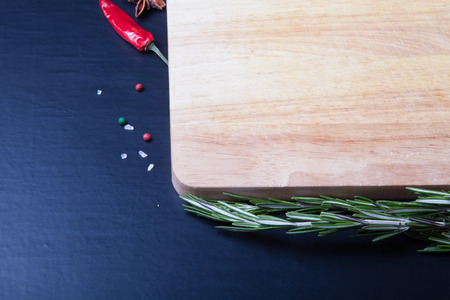 Cutting board with rosemary, colored and chili pepper, and sea salt on a black background. Toned. photo
