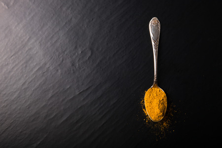 Old metal spoon with spices on a black background.