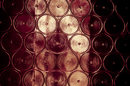 metall and glass: Wall of glass bottles with somthing metall behind it. Selective focus. Toned. Stock Photo